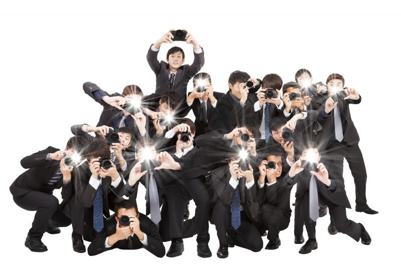 many photograper holding camera pointing to you and isolated on white
