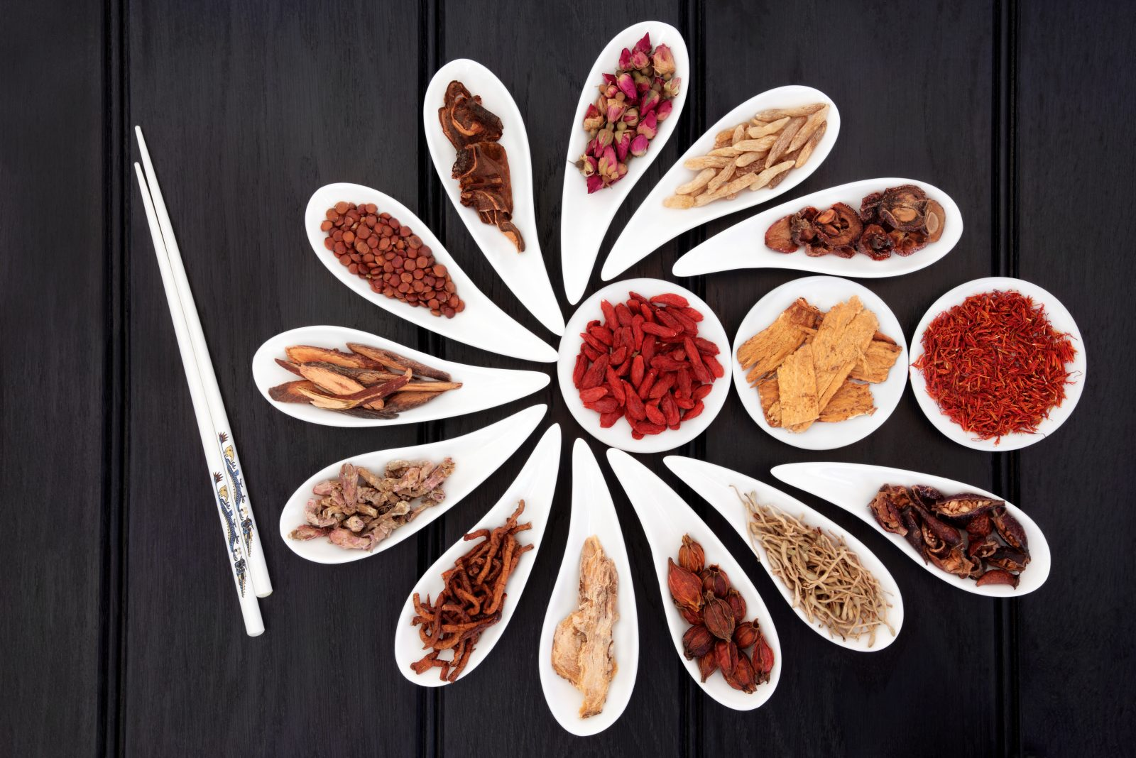 Chinese herbal medicine selection in white china bowls with chopsticks.